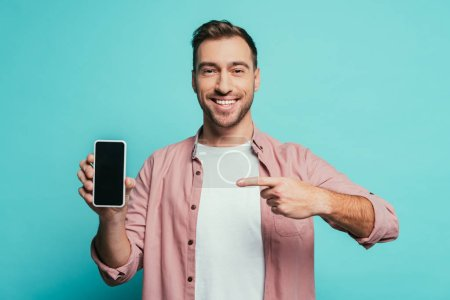 smiling man pointing at smartphone with blank screen, isolated on blue