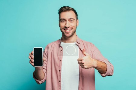 cheerful man showing thumb up and smartphone with blank screen, isolated on blue