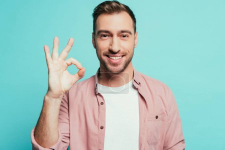 Photo for Cheerful handsome man showing ok sign, isolated on blue - Royalty Free Image