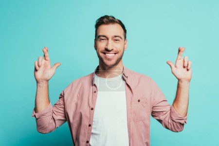 Photo for Cheerful handsome man with fingers crossed isolated on blue - Royalty Free Image