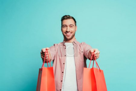 Photo for Smiling man holding shopping bags, isolated on blue - Royalty Free Image