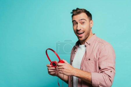 Photo pour Homme excité tenant des écouteurs, isolé sur bleu - image libre de droit