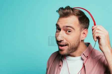 Photo pour Un homme barbu positif écoutant de la musique avec écouteurs, isolé en bleu - image libre de droit