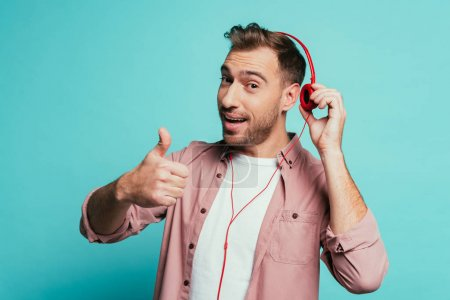 happy man listening music with headphones and showing thumb up, isolated on blue
