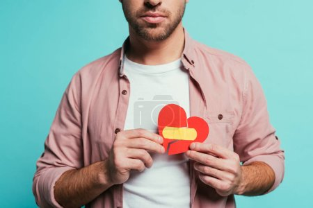 Photo for Cropped view of upset man holding broken heart with plaster, isolated on blue - Royalty Free Image