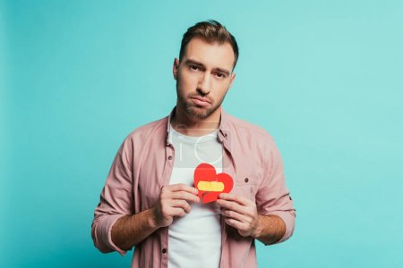 Photo for Upset man holding broken heart with plaster, isolated on blue - Royalty Free Image