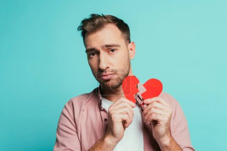 Photo for Upset man holding broken heart, isolated on blue - Royalty Free Image