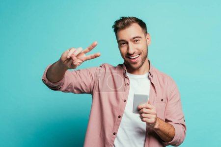 Photo for Happy man using smartphone and showing peace symbol, isolated on blue - Royalty Free Image