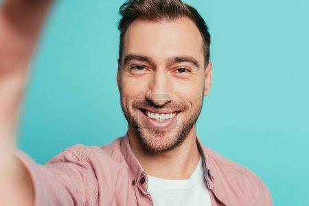 Photo pour Bel homme souriant prenant selfie, isolé sur bleu - image libre de droit