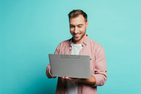 cheerful bearded man using laptop, isolated on blue