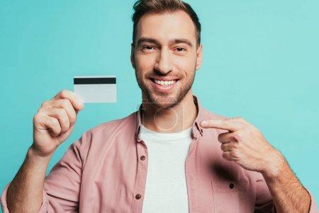 Photo pour Homme barbu heureux pointant vers la carte de crédit, isolé sur bleu - image libre de droit