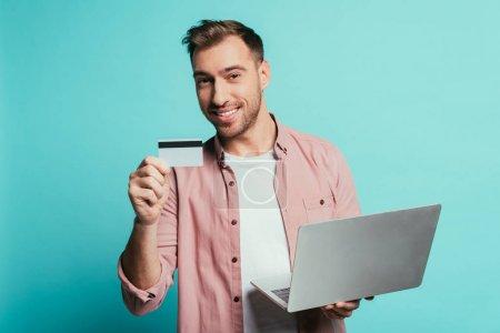 Photo pour Homme barbu magasinant en ligne avec carte de crédit et ordinateur portable, isolé sur bleu - image libre de droit