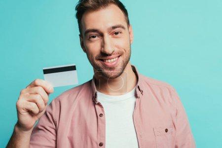 Photo pour Homme barbu heureux tenant la carte de crédit, isolé sur bleu - image libre de droit