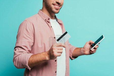 Photo pour Vue croisée d'un homme magasinant en ligne avec un smartphone et une carte de crédit, isolé en bleu - image libre de droit