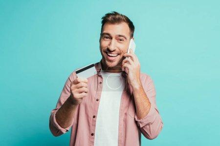 Photo pour Homme souriant faisant ses achats en ligne avec son téléphone intelligent et sa carte de crédit, isolé en bleu - image libre de droit