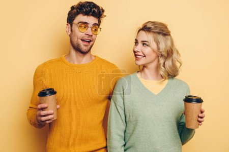 Photo for Happy man and woman looking at each other while holding coffee to go on yellow background - Royalty Free Image