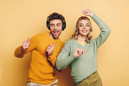 happy couple dancing while listening music in wireless headphones on yellow background