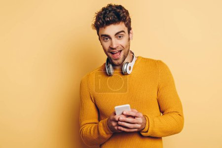 handsome man with wireless headphones on neck using smartphone and smiling at camera on yellow background