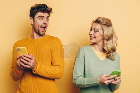 smiling man and woman looking at each other while chatting on smartphones on yellow background