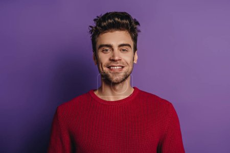 Photo for Young, handsome man smiling at camera on purple background - Royalty Free Image