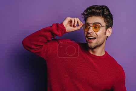 cheerful man touching glasses while looking away on purple background