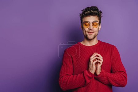 Photo for Cunning man gesturing with joined fingers on purple background - Royalty Free Image
