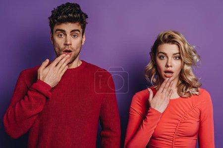 Photo pour Un homme et une femme choqués regardant la caméra sur fond violet - image libre de droit