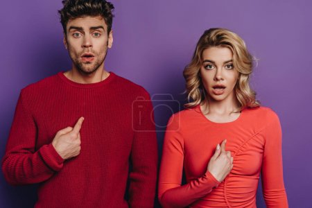 Photo for Surprised man and woman pointing with fingers at themselves while looking at camera on purple background - Royalty Free Image
