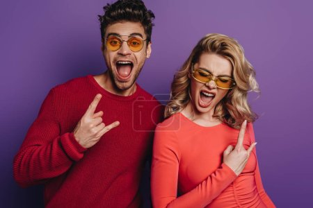 Photo for Excited man and woman showing rock signs on purple background - Royalty Free Image