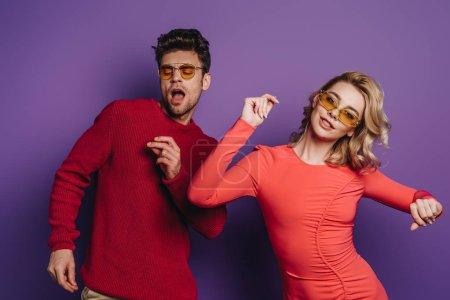 heureux jeune couple dansant sur fond violet