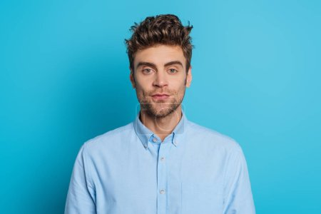 positive young man in blue shirt looking at camera on blue background