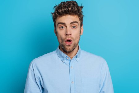 shocked young man looking at camera while standing with open mouth on blue background