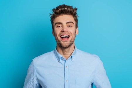 Photo pour Jeune homme gai qui rit en regardant la caméra sur fond bleu - image libre de droit