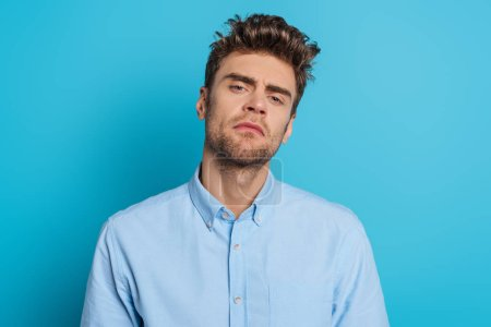 Photo for Young, skeptical man looking at camera on blue background - Royalty Free Image