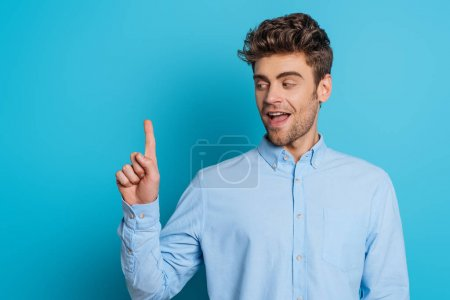 Photo for Positive man smiling and showing idea gesture on blue background - Royalty Free Image