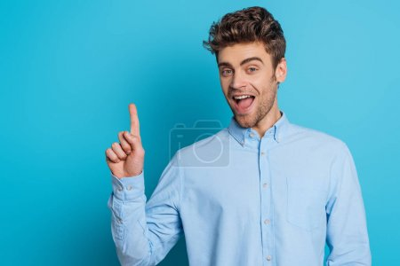 Photo for Cheerful man showing idea gesture while smiling at camera on blue background - Royalty Free Image