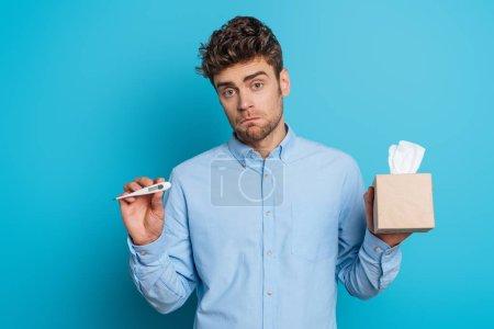 Photo pour Un jeune homme malade tenant un paquet de serviettes en papier et montrant un thermomètre sur fond bleu - image libre de droit