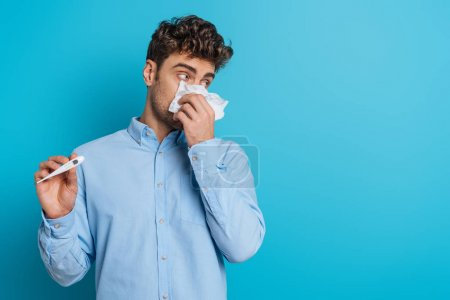 Photo pour Un jeune homme malade essuyant son nez avec de la serviette de papier et montrant un thermomètre sur fond bleu - image libre de droit