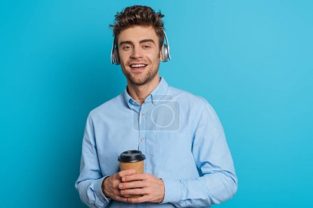 Photo for Cheerful young man smiling at camera while listening music in wireless headphones and holding coffee to go on blue background - Royalty Free Image