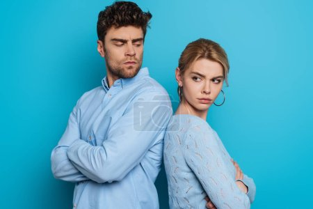 Photo for Offended man and woman standing back to back with crossed arms on blue background - Royalty Free Image