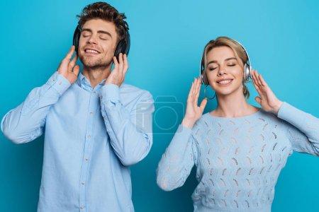 Photo pour Homme et femme heureux écoutant de la musique dans des écouteurs sans fil les yeux fermés sur fond bleu - image libre de droit