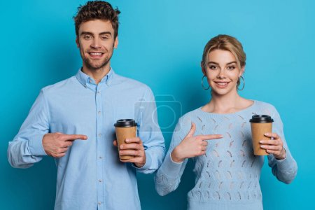 Photo for Smiling man and woman pointing with fingers at disposable cups while looking at camera on blue background - Royalty Free Image