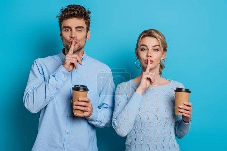 Photo pour Jeune homme et femme montrant des signes de silence tout en tenant du café pour aller sur fond bleu - image libre de droit