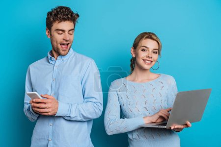 Photo for Cheerful man chatting on smartphone and looking at girlfriend using laptop on blue background - Royalty Free Image