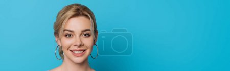 Photo pour Photo panoramique d'une jolie et joyeuse fille souriante à la caméra sur fond bleu - image libre de droit
