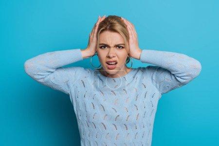 Photo pour Fille mécontente toucher la tête tout en souffrant de migraine sur fond bleu - image libre de droit