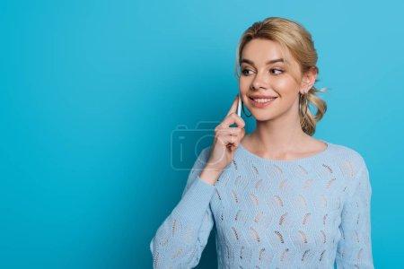lächelndes Mädchen, das wegschaut, während es auf blauem Hintergrund mit dem Smartphone spricht