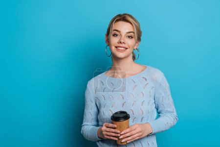 cheerful girl smiling at camera while holding coffee to go on blue background