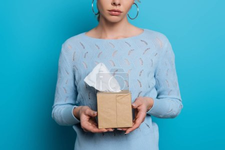 Photo for Cropped view of upset girl holding pack of paper napkins on blue background - Royalty Free Image