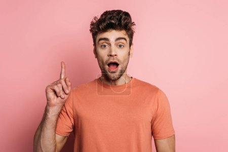 Photo for Shocked man showing idea sign while looking at camera on pink background - Royalty Free Image
